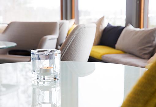 Kahvilan lasipöytä, jolla tuikkukynttilä lasisessa tuikkukupissa. Vaaleat tuolit, taustalla ikkunapenkkien keltaisia, tummansinisiä ja vaaleita tyynyjä. Kuva on valoisa ja välittää kahvilan modernin tunnelman.