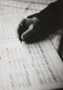 Jean Sibeliuksen käsi ja nuottipaperi. Jean Sibelius tekee lyhyellä lyijykynällä merkintöjä nuottipaperiin, paperilla näkyvyy useita nuottirivejä. Vanha, mustavalkoinen kuva Museoviraston kokoelmasta.