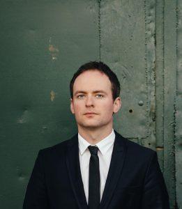 Pianisti Mihkel Järvi, puolivartalokuva vihreää ovea vasten.