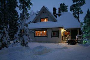 Ainola talvisessa iltahämärässä, valot hohtavat ikkunoista jamaa ja katto ovat lumen peitossa