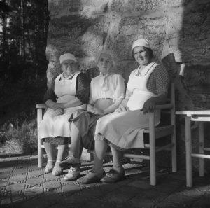 Mustavalkoinen kuva 1940-luvulta, jossa vasemmalta oikealle istuvat penkillä Helmi Vainikainen, Aino Sibelius ja Aino Kari